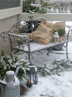 Winter snow covering metal outdoor bench decorated with pillows,lanterns and greenery