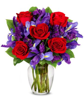 Purple Ruby Passion  $59.99  Rubies are red...and so are the roses in this romantic arrangement all set to take someone's breath away. Purple statice, blue iris and a lovely clear garden vase also contribute effortlessly to a look of total beauty.