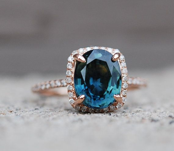 Blue Green sapphire Rose gold engagement ring. Engagement ring by Eidelprecious. This ring features a 3.9ct cushion sapphire. The color is gorgeous deep peacock green with blue flashes , SI, heated. The sapphire is very beautiful and clean, tones of sparkles! The sapphire displays color change and looks more green under natural light and more blue under electric light. This beauty is set in a 14k rose gold diamond setting.  This sapphire is set into my signature 14k rose gold setting…