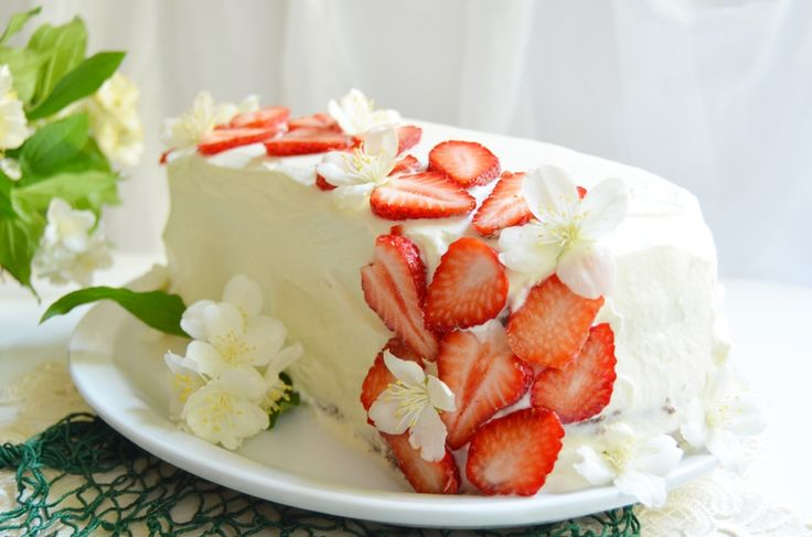 A simple cake with whipped cream and strawberries.