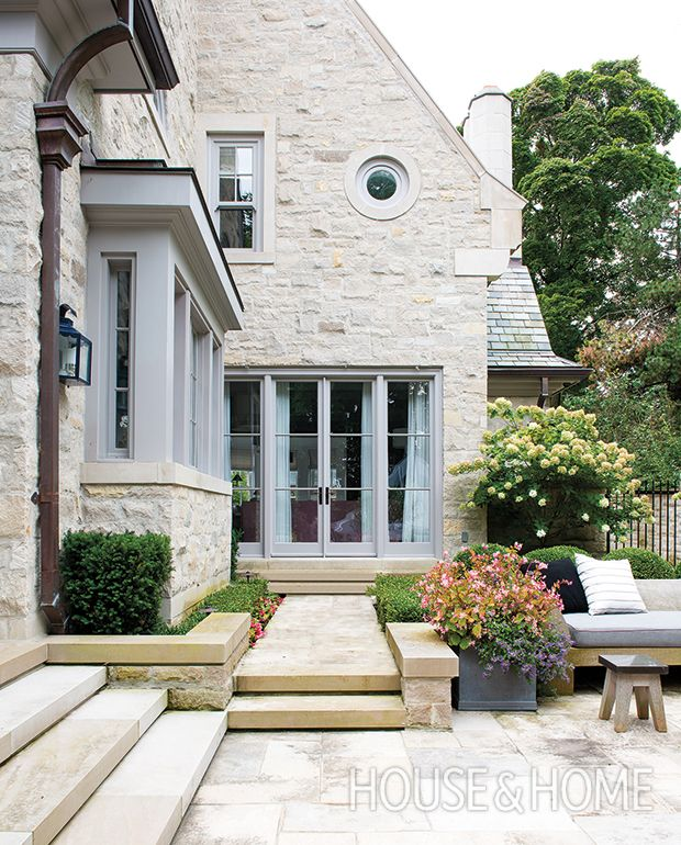 This home's façade, made of Indiana cut limestone and rubble stone, is a cohesive backdrop for elegant patios and paths. | Photographer: Alex Lukey | Designer: Katherine Newman