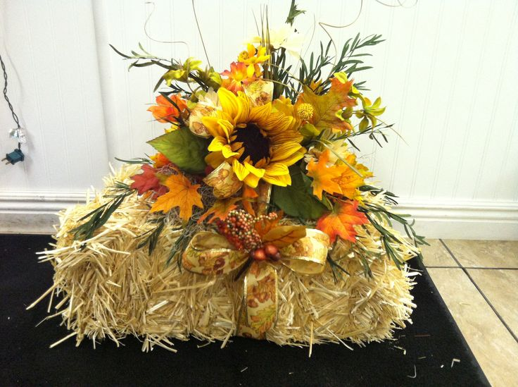 Silk flowers nicely arranged on a small hay bale this for Fall fake flower arrangement ideas