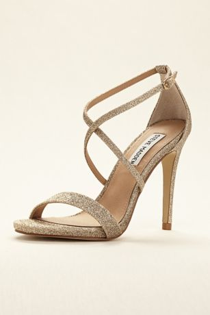 "Versatile and fun! These Steve Madden strappy sandals are the perfect go-to sandal for any event.  Sandal features crisscross straps in Glitter Gold and Iridescent Silver.  Heel height: 4""  Fully lined. Buckle closure. Imported"