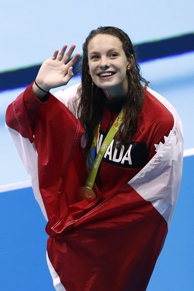 #RIO2016 Canada's Penny Oleksiak waves while wrapped in her national flag during the medal ceremony of the Women's 100m Freestyle Final during the swimming...