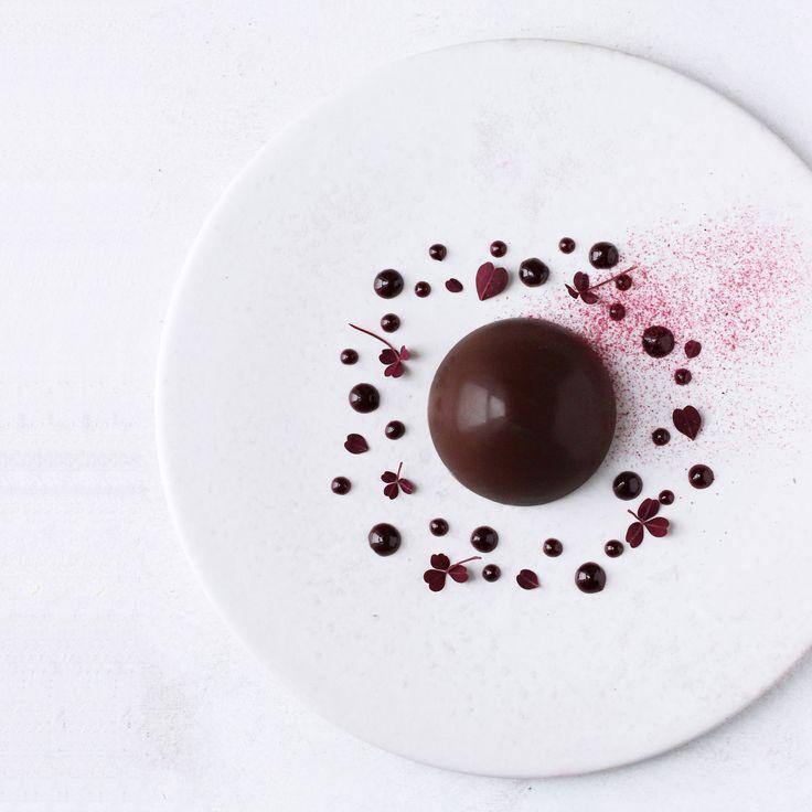 Cremet vaniljeparfait, knasende mørk chokoladeskal, syrligsød solbærsirup, solbærstøv og rød skovsyre. Kæmpe Eskimo i lækre, nye klæder.