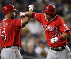 Mike Trout #27 of the Los Angeles Angels of Anaheim celebrates with Albert Pujols #5 after hitting a solo home run in the fourth inning against the Los Angeles Dodgers at Dodger Stadium in Los Angeles, California.