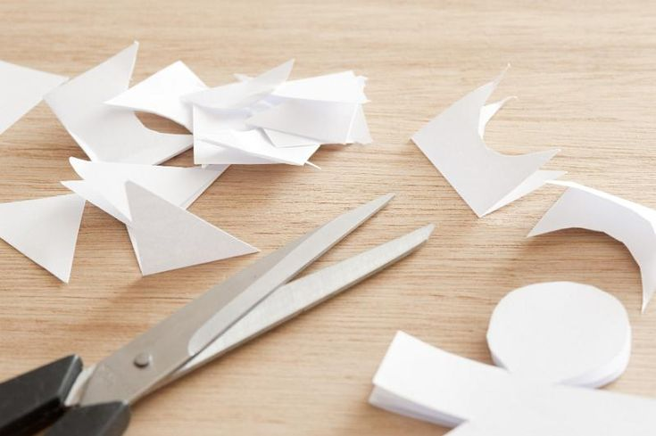 Paper craft concept with a pair of scissors and cut out of a doll or figure lying on a wooden table - free stock photo from www.freeimages.co.uk