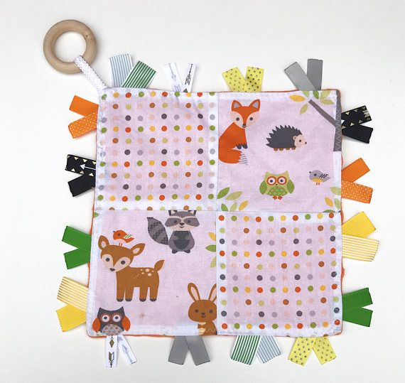 This mini woodland animals tag quilt blanket with fox, hedgehog, and owl would make a great gift for any baby or toddler. Each tag is cut and heat fixed for an added sensory experience. With its soft minky backing and smooth cotton front it makes a great toy for baby to enjoy.  Colors: Orange, Green, Yellow Materials: Cotton, Minky, Wood Ring, Ribbon Measurements: 9 in x 9 in Care: Spot clean as needed  *Contains organic coconut oil as a wood finisher*  If you do not see what you are looking…
