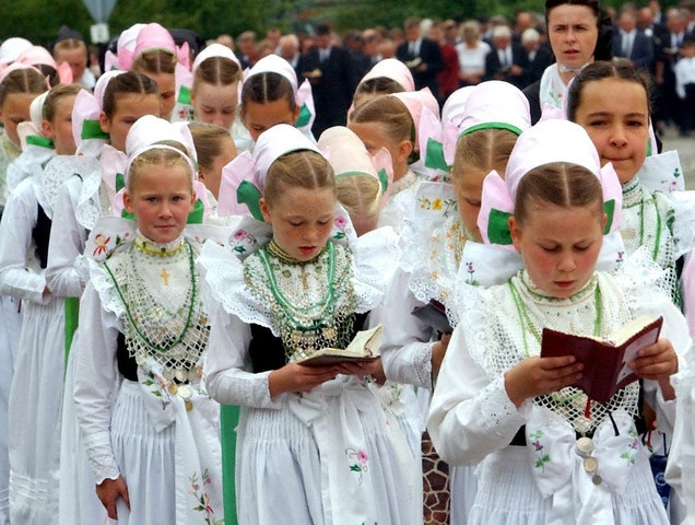 19 Jun 2003, Crostwitz, Saxony, Germany --- A Sorbian procession celebrating the Feast of Corpus Christi is led by a group of bridesmaids and marches through the town. The procession of the Catholic Sorbs is traditonally led by bridesmaids, the so called 'Druschki', who are dressed in their traditional costumes. The Feast of Corpus Christi is a religious Catholic holiday which celebrates the body and blood of Jesus Christ.