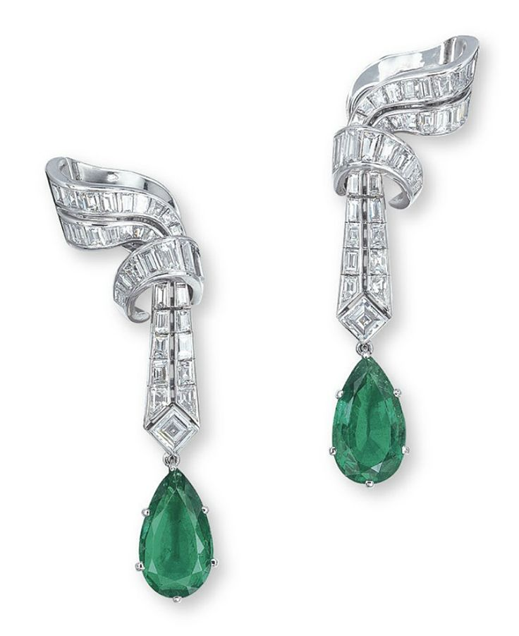 A PAIR OF EMERALD AND DIAMOND EAR PENDANTS, BY VAN CLEEF & ARPELS EACH SET WITH A PEAR-SHAPED EMERALD WEIGHING APPROXIMATELY 3.82 AND 3.81 CARATS, JOINED TO THE SQUARE, BAGUETTE AND WHISTLE-CUT DIAMOND SCROLLING SURMOUNT, MOUNTED IN 18K WHITE GOLD, 5.3 CM LONG, WITH FRENCH ASSAY MARK FOR GOLD. Signed