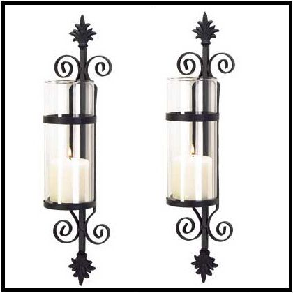 """2 FLEUR DE LES CYLINDER CANDLEHOLDERS A palatial touch of Tuscan elegance adds old-world beauty to your home! Ornate matte-black forms a dramatic backdrop for a crystal-clear column of glass. Simply add your favorite color pillar candle for instant decorating magic! Metal with glass. Candle not included. 4 1/4"""" x 4 1/2"""" x 19 3/4"""" high."""