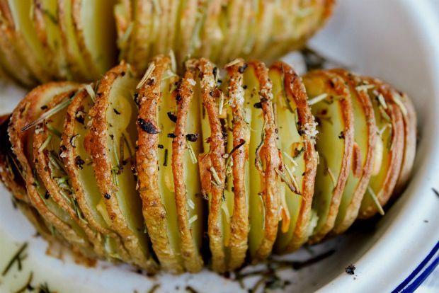 Και πώς αλλιώς να φτιάξεις τις πατάτες; Ψητές αλλά κομμένες σαν πτυχές βεντάλιας: σκόρδο και μυρωδικά σφηνώνονται ανάμεσα στις ροδέλες και σε λιγότερο από ώρα έχεις μυρωδάτα πατατάκια που, τσίμπα - τσίμπα, ούτε πηρούνι δεν θα προλάβεις να λερώσεις για χάρη τους.