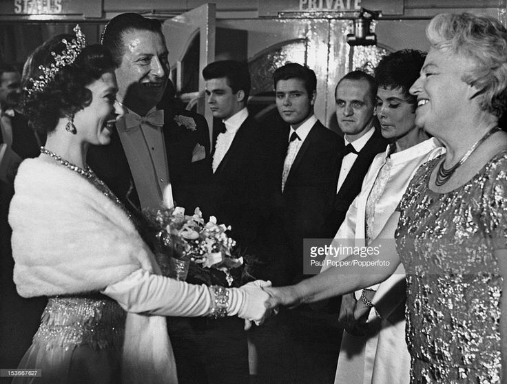Queen Elizabeth II shakes hands with English singer Gracie Fields (1898 - 1979) at the Royal Variety Performance at the London Palladium, 2nd November 1964. Left to right: The Queen, impresario Bernard Delfont (1909 - 1994), bassist John Rostill (1942 - 1973) of the Shadows, singer Cliff Richard, American comedian Bob Newhart, American singer Lena Horne (1917 - 2010) and Fields.