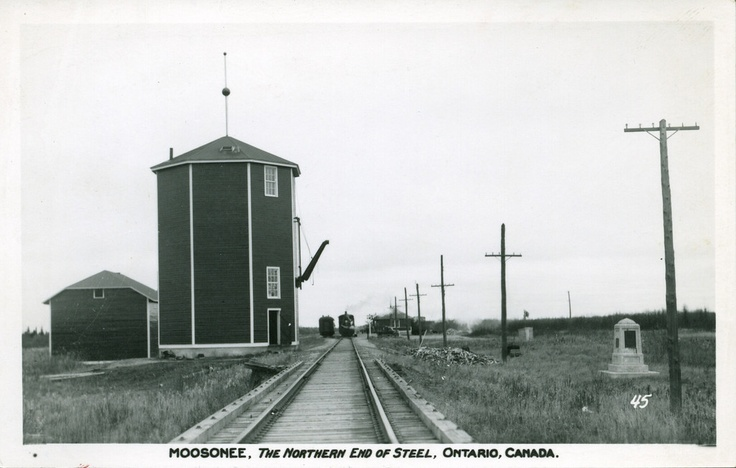 Postcard: Moosonee. Looking from Store Creek bridge to station. Showing memorial cairn, water tower for steam locomotives.