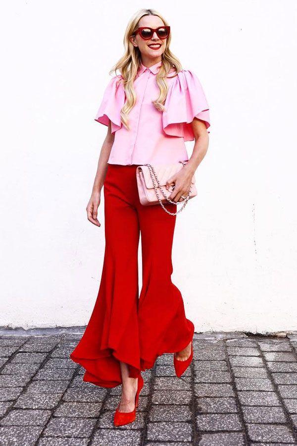 Look combinando duas cores: rosa e vermelho, usando calça de babados, camisa de babados e scarpin.