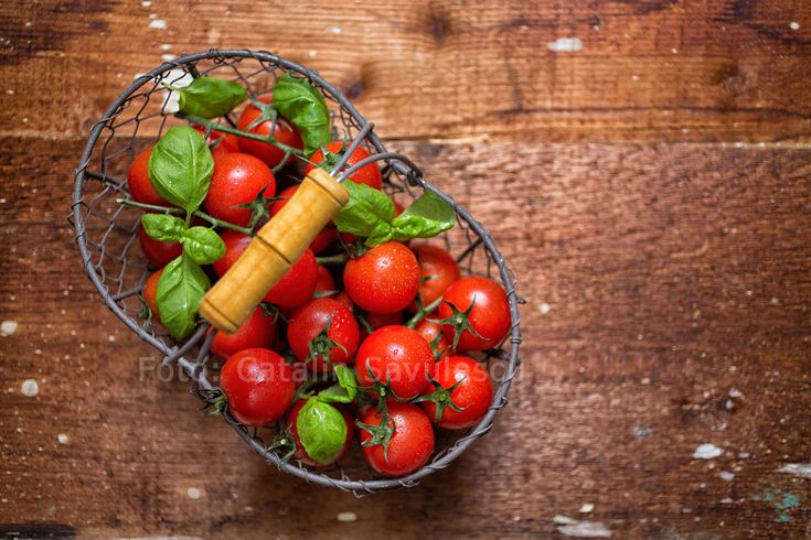 Tomatoes with fresh basilicum leaves in a metallic basket placed on a wooden surface.