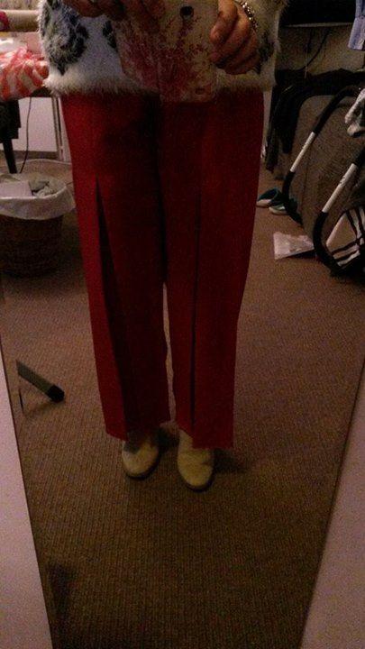 Rode broek met stolpplooien op de voorpijp