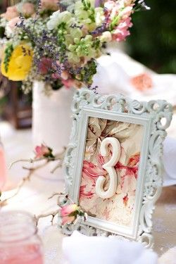 DIY table numbers - love the floral fabric used here {frames + fabric + wooden numbers}