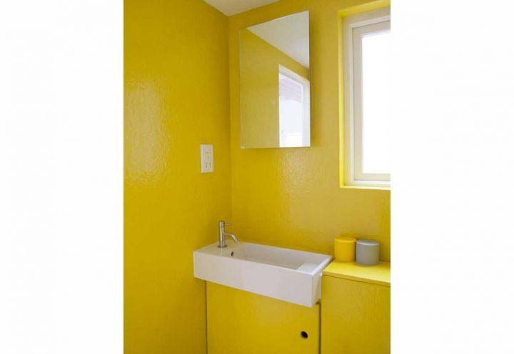 Uno dei due bagni dell'abitazione disegnata a Londra da Studiomama, caratterizzato dal vivace rivestimento in giallo. Date le dimensioni modeste, la parola d'ordine di questa stanza è funzionalità