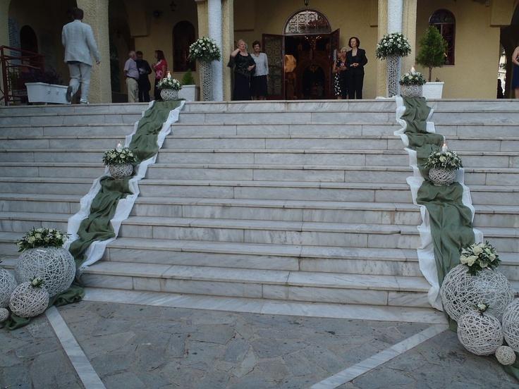 Εξωτερικός στολισμός γάμου στην εκκλησία στα σκαλιά της με λαδί και λευκά υφάσματα, και πάνω τους λευκές μπάλες μπαμπού με συνθέσεις με ελιά, τριαντάφυλλα σε λευκό.