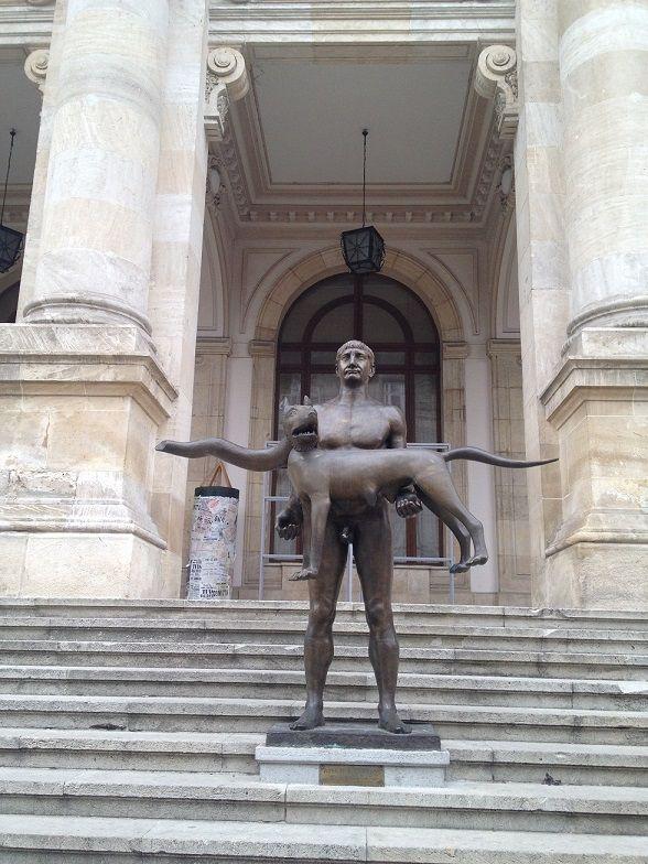 Estátuas de Bucareste, capital da  Romênia. As estátuas de Bucareste são por si só uma atração. A cidade é cheia delas! Algumas bonitas, algumas modernas, outras antigas, mas curiosamente, muitas bizarras. Esta estátua de um homem de aparência estranha e feia, que desajeitadamente segura este meio-lobo-meio-cobra foi eleita pelos locais como a estátua mais feia da cidade. Fica em frente ao Museu Nacional de História.
