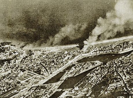 This aerial photograph shows the town of Dieppe during the raid of Aug. 19, 1942. Smoke rises from burning landing craft and from buildings facing the beach where the Churchill tanks of The Calgary Regiment landed. Dieppe's harbor can be seen in the foreground of the photograph.