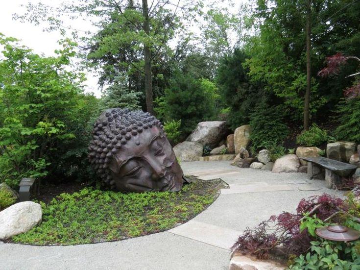 jardin asiatique de style japonais, statue de Bouddha en métal noir, grosses pierres naturelles et banc assorti