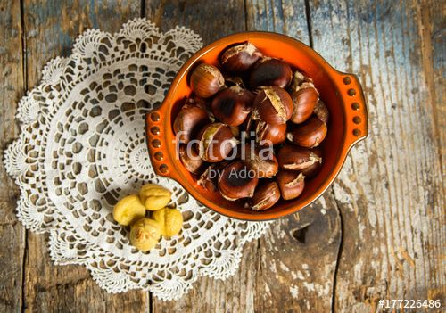 """Download the royalty-free photo """"Roasted chestnuts in a bowl on old wooden table. top view """" created by stillforstyle at the lowest price on Fotolia.com. Browse our cheap image bank online to find the perfect stock photo for your marketing projects!"""