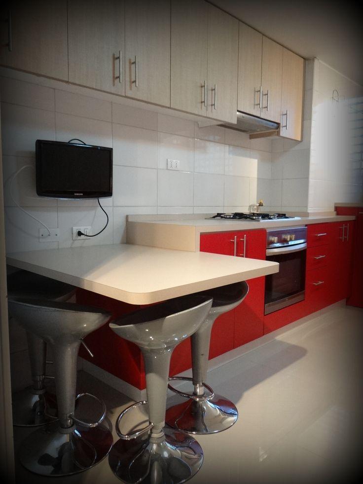 Cocina remodelada en dos tonos, con cubierta post formada, lavaplatos empotrado y espacio para secadora y lavadora oculto tras puertas. Mesa península postformada.