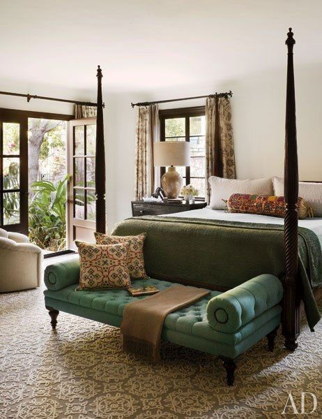 The master suite of a 1930s Los Angeles home by design firm Commune is furnished with a George Smith button-tufted bench in an Osborne & Little fabric. The embroidered bolster pillow on the bed is from Hollywood at Home, the curtains are made of a Lee Jofa linen, and the carpet is by Tai Ping.Pin it.