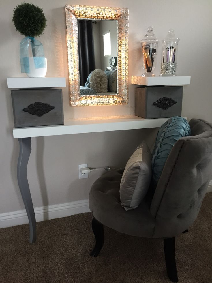 My homemade vanity. I pieced together items to make it and was able to do it much more cheaply than buying a vanity table. It's made up of one long and two shorter Lack shelves and two Lalle legs from IKEA. The shelves were only $14.99 for the long one and $6.99 each for the short ones and the legs were $12.50 each. I used IKEA Dioder lights (which are made to go around a TV) and stuck them around an existing mirror that I had. I found the grey boxes at Michael's and got both for only $25.00