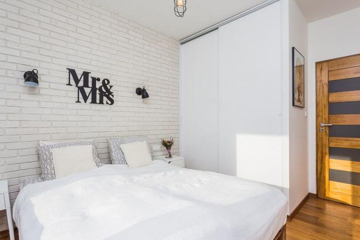 Aranżacja niewielkiej sypialni w stylu skandynawskim. Białe cegły na ścianie dodatkowo eksponują czarną dekorację i...