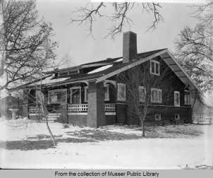 Huttig Mfg. Co. Muscatine :: Musser Public Library Oscar Grossheim Photo Archive Collection. Jan. 28, 1920. This Craftsman style bungalow has a long sloping roof with exposed rafters and a dormer with a shed roof. The porch columns are made of brick as is the foundation. A chimney towers over the structure near the front of the house. Large picture windows with small divided spaces at the top can be seen under the porch roof. A cement bird bath sits to the left of the photograph.