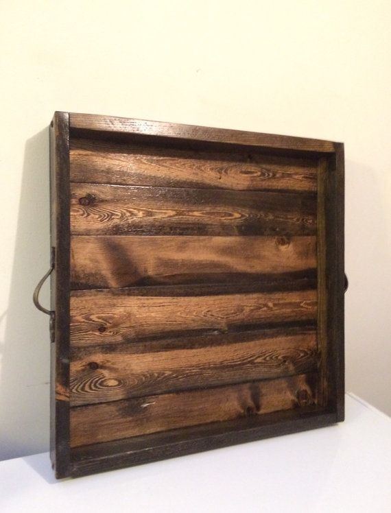 This rustic ottoman tray is made of pine. Perfect to sit on your ottoman for a hard surface for entertaining. It measures 20 x 20 x 21/2 on the outside. This tray is stained with Minwax Jacobean, 3 in 1 stain, sealer, and protectant. It has 2 coats of lacquer over the entire tray. If you like rustic, this is the ottoman tray for you! Handles can be customized, as I have a large variety to choose from.  This is a very sturdy tray, made with <3. This would not be your exact tray, but it will…
