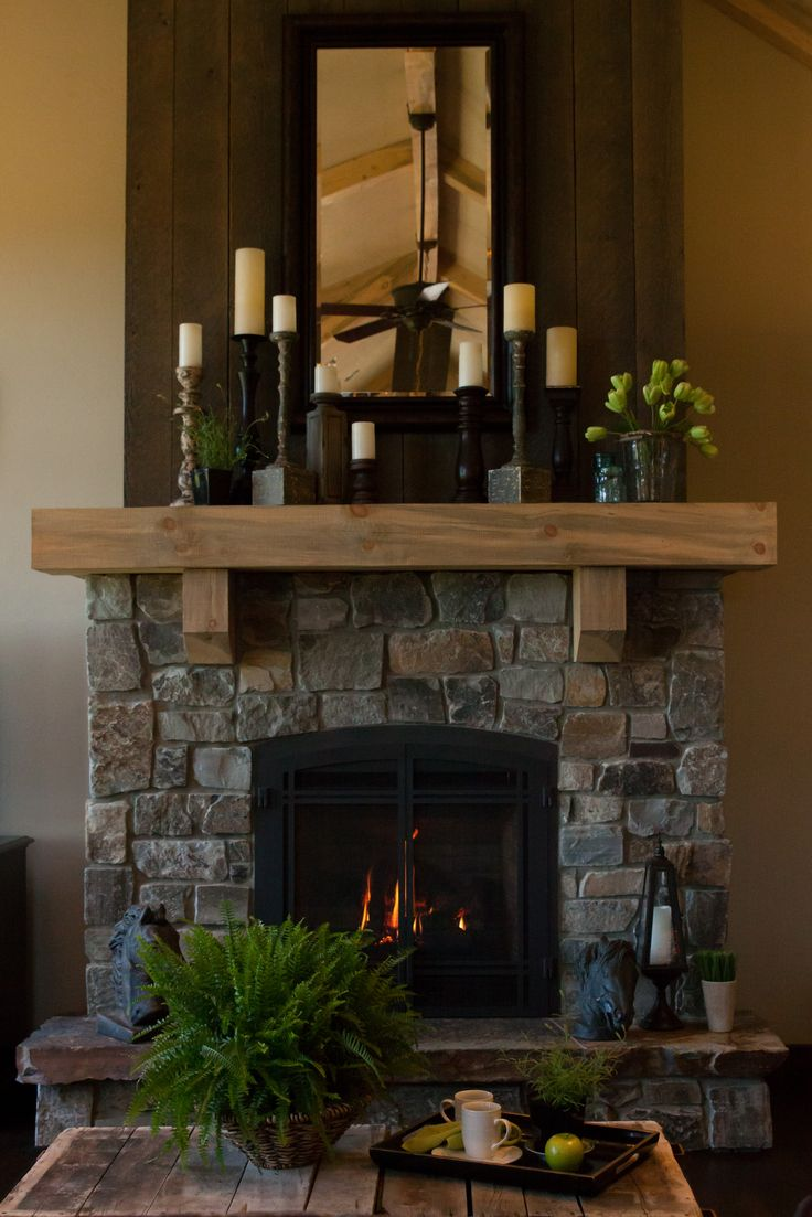 Blue, greys and rust colors permeate the natural Montana rock fireplace. Greyed, rough sawn wood seems to be upholstered on the chimney wall above the beam mantel. The Suenram's chose Montana Timber Company for their wood paneling throughout the home and on the exterior siding.