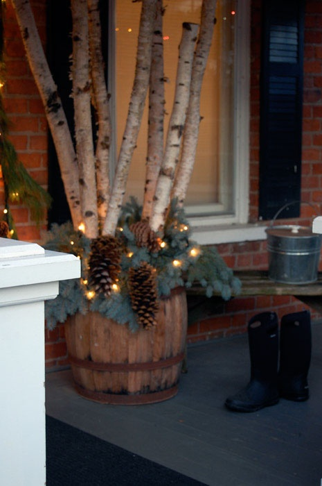 Birch logs uprighted in a barrel with greenery, pinecones and lights!!!! Gorgeous!