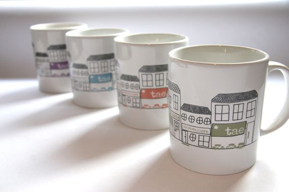 Mainstreet Mug  In a choice of three colourways these mugs depict a fictitious streetscape of tea and coffee shops. The colours are inspired by the pastel shades of masonary paint used on many Irish mainstreets.