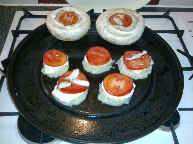 """gekookte, gepureerde bloemkool met kruiden en 2 eieren erdoor als vulling in de champignons en als bodem voor de mini pizza's. Op de bodems mozzarella en tomaat. Probeer de bloemkool """"droog"""" te houden door het beetgaar en koud te blenderen."""