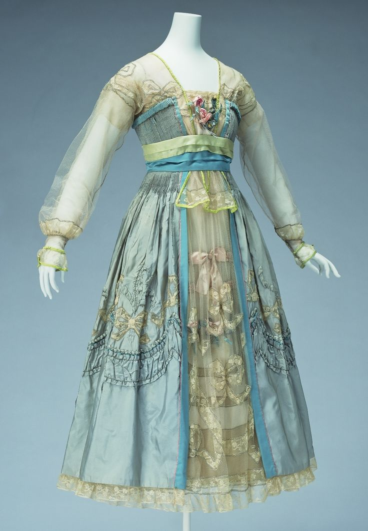 Evening Dress 1916 Lucy Christina Wallace Dress characterized by pale colouring and delicate decoration. The skirt section is three-layered, with the front opening of the overskirt giving glimpses of...