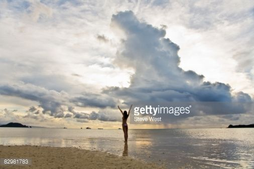 Stock Photo : Woman standing on beach with arms raised up