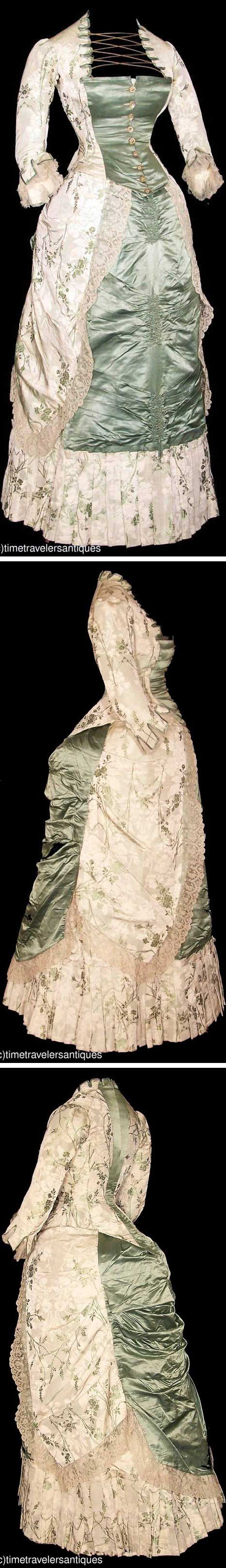 Dress, ca. 1880. Sage green floral silk brocade two-piece bustle gown with fern green accents & moss green silk satin panels. Silk cord laced design criss-crosses decolletage with tab accents that repeat at cuffs, which have pleated silk chiffon inserts. Lined bodice has deep points at hem & decorative floral metal buttons at front closure. Ruched & pleated front panel on skirt; draped bustled back to attached overskirt, trimmed in blonde Chantilly lace. time-travelers/ebay