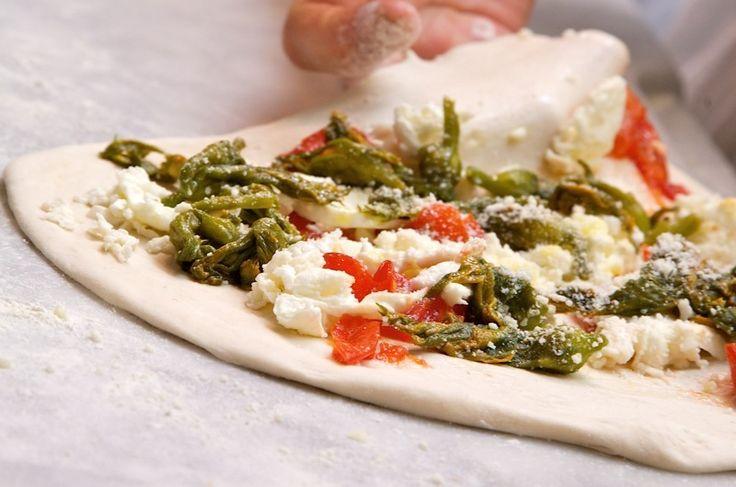 Pizza con fiori di zucca prima della cottura;