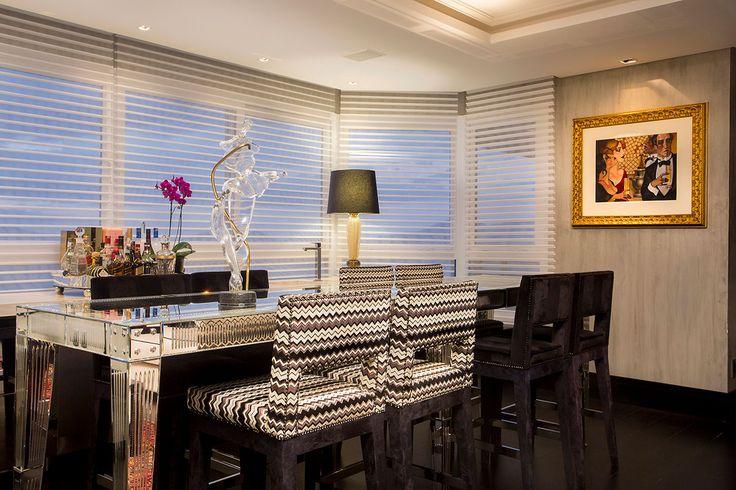 Decoração de apartamento com mix de estilos, na sala de jantar com mesa de jantar espelhada, banquetas estofadas, escultura, obra de arte, bar, bar em casa.