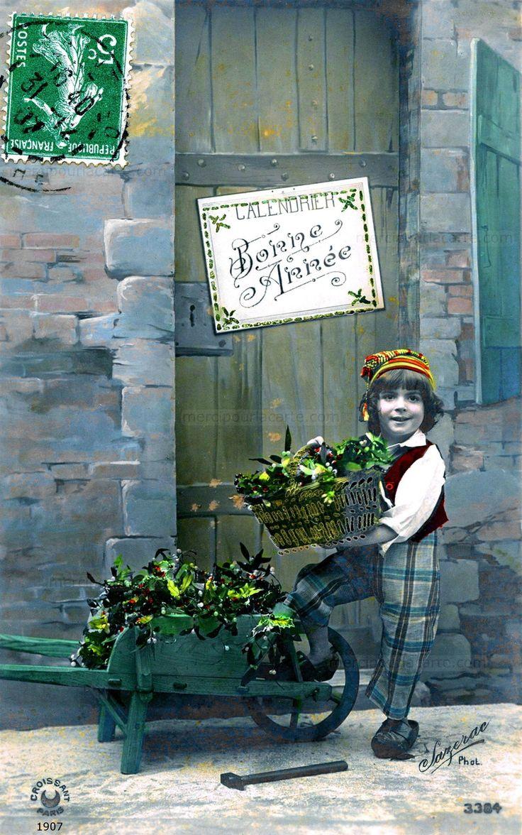 Bonne Année - Devant une porte un garçon présente une corbeille et une brouette remplies de houx et de gui - 1907 (from http://mercipourlacarte.com/picture?/1529/)