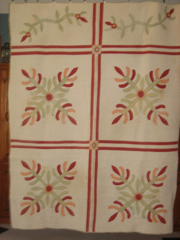 """I don't know the name of this applique pattern - maybe Christmas Cactus?   The applique is done by hand. The big blocks are pieced/sashed by machine, and the quilting all done by hand. It's in very good condition! It is about 69""""x89""""."""