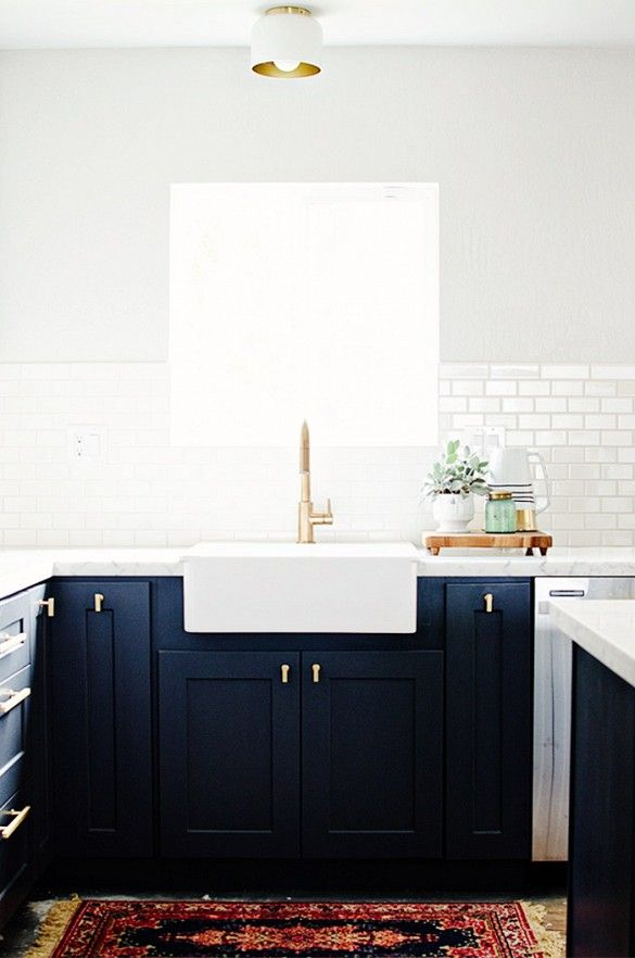 Decorating Your First Home? Here's Where to Start via @domainehome- black cabinets, apron front sink, gold faucet and hardware, white subway tile and persian rug