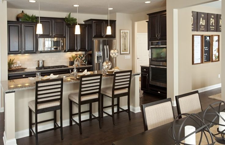 Compact kitchen with dark cabinetry and island kitchens for Galley kitchen with breakfast bar