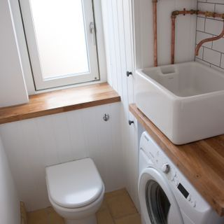 Space-saving in the smallest room: short projection back-to-wall WC with concealed cistern, boxed-in boiler with tongue and groove effect mdf, shallow depth washing machine (7kg capacity but only 40cm deep) and reclaimed Belfast sink over.