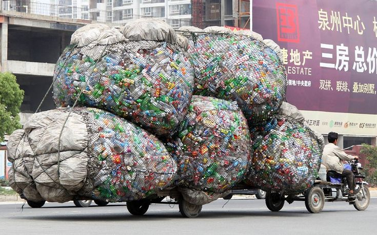 A man drives a motorised tricycle carrying bags of plastic bottles for recycling in Jinjiang, China