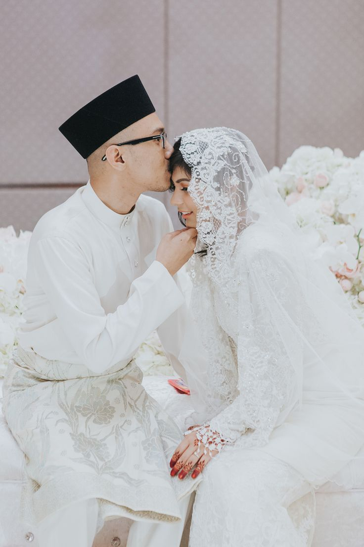 Groom in traditional white Muslim attire kissing his bride on the forehead // Andy and Hanis' wedding celebrations began with a Bollywood-themed henna night, and was followed by a traditional 'akad nikah' (or wedding solemnisation) and two receptions.